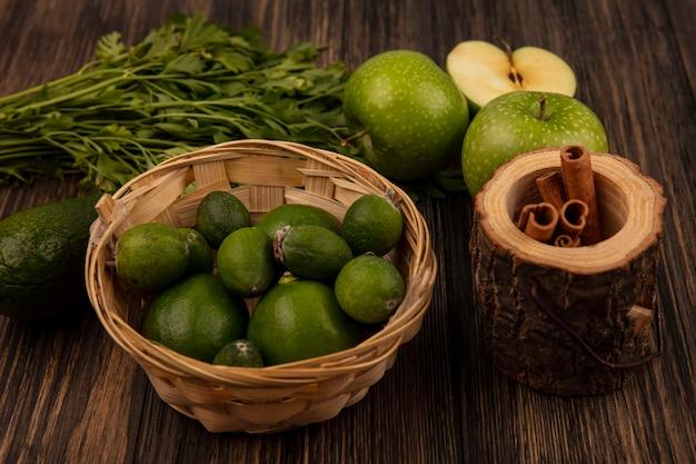 Vista dall'alto di fresche e mature feijoas su un secchio con bastoncini di cannella su un vaso di legno con mele e avocado isolato su una parete in legno