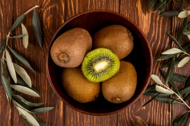 Top view of fresh ripe kiwi fruits in a wooden bowl on rustic