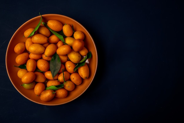 Top view of fresh ripe kumquats on a plate on black surface with copy space