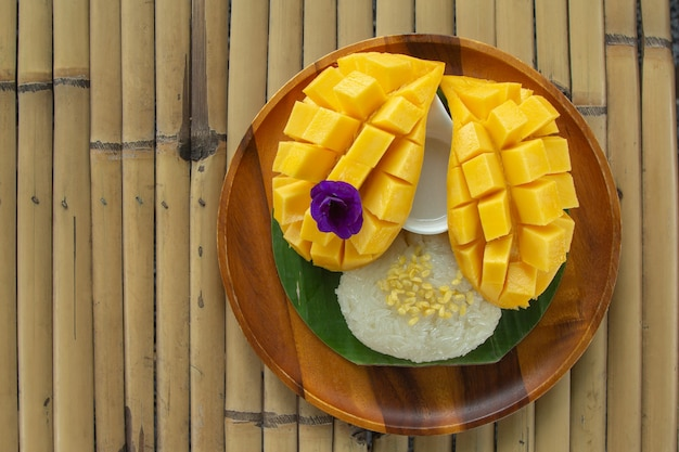 Top view of fresh ripe mango and sticky rice with coconut milk on bamboo