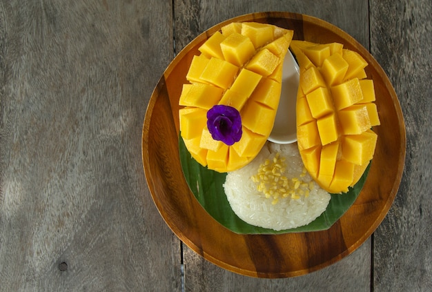 Top view of fresh ripe mango and sticky rice with coconut milk on wooden