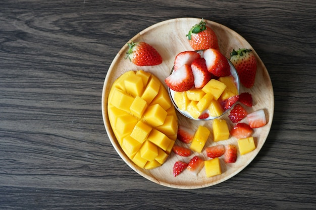 Top view fresh ripe mango and strawberry fruit in a cup with cookies soy yogurt in a wooden plate