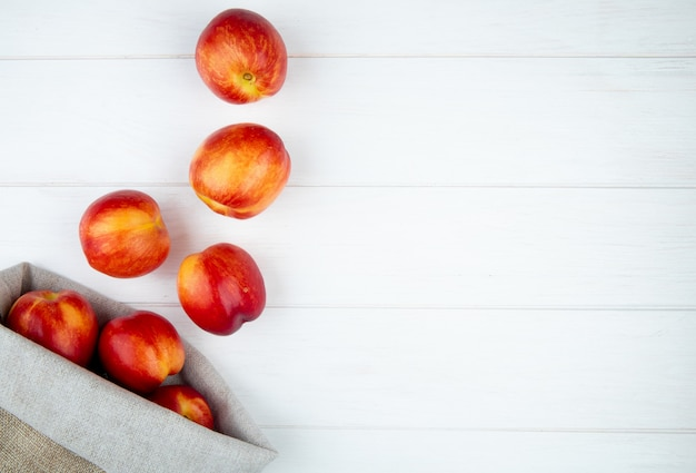 Top view of fresh ripe nectarines scattered from a sack on white surface with copy space