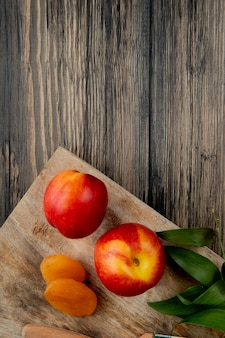 Top view of fresh ripe nectarines with dried apricots on wooden cutting board on rustic background with copy space