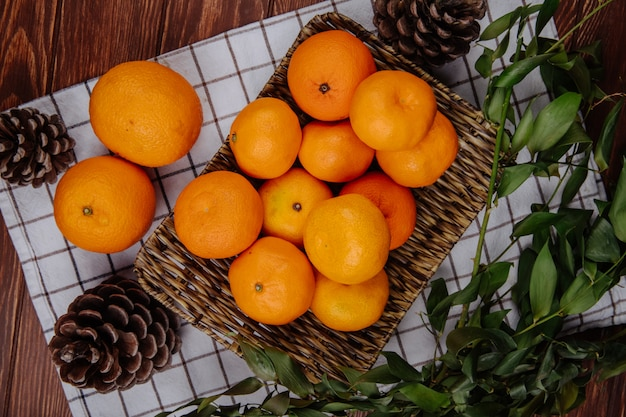 Top view of fresh ripe oranges on a wicker tray and cones on plaid tablecloth on wooden surface