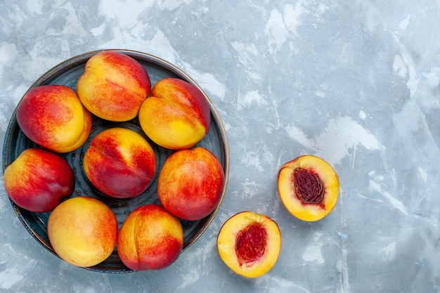 Top view fresh ripe peaches delicious summer fruits on light-white desk