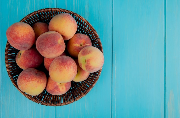 Top view of fresh ripe peaches in a wicker basket on blue wooden background with copy space