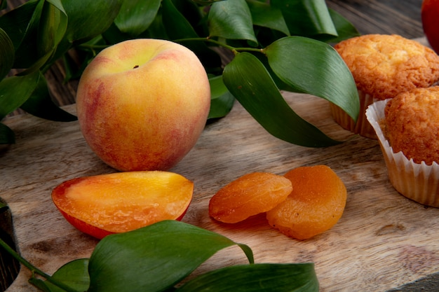 Top view of fresh ripe  peaches with dried apricots on wooden background