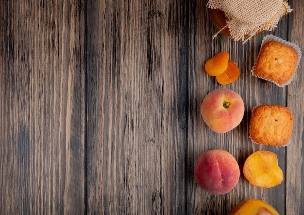 Top view of fresh ripe peaches with muffins and peach jam in a glass jar on rustic wooden table with copy space