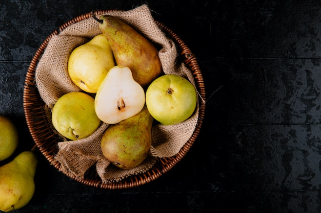 Top view of fresh ripe pears in a wicker basket on black background with copy space