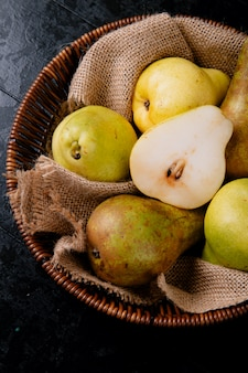 Top view of fresh ripe pears in a wicker basket on black background