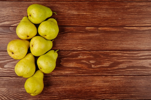 Top view of fresh ripe pears on wooden background with copy space