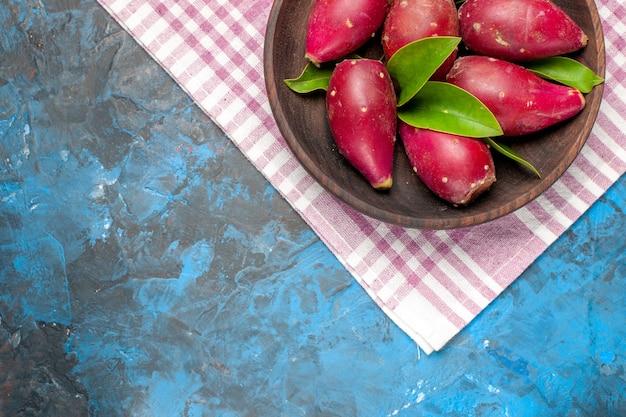 Vista dall'alto prugne mature fresche all'interno del piatto sullo sfondo blu
