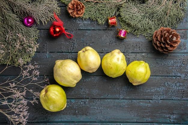 Vista dall'alto mele cotogne mature fresche frutti acidi su scrivania rustica blu scuro pianta fresca frutta matura molti alberi