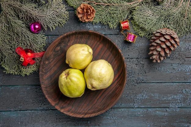 Top view fresh ripe quinces sour fruits inside plate on a dark-blue rustic desk fresh plant ripe tree fruit