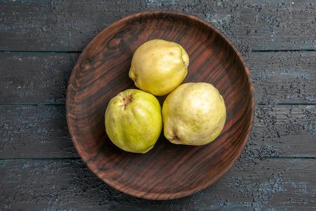 Vista dall'alto mele cotogne mature fresche frutti acidi all'interno del piatto su albero da frutto rustico blu scuro da scrivania pianta fresca matura