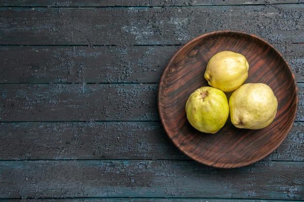 Top view fresh ripe quinces sour fruits inside plate on a dark blue rustic desk plant fruit tree ripe fresh