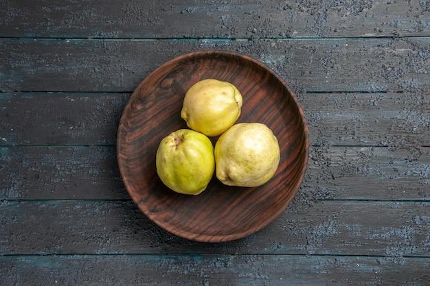 Vista dall'alto mele cotogne mature fresche frutti acidi all'interno del piatto su albero da frutta rustico blu scuro da scrivania pianta fresca matura