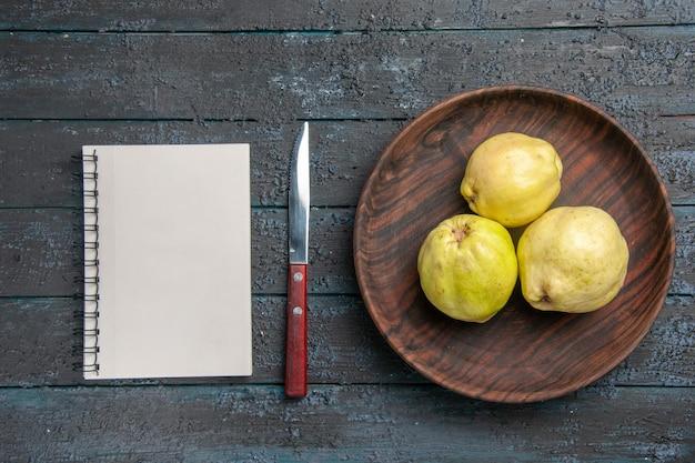 Vista dall'alto mele cotogne mature fresche frutti acidi all'interno del piatto su piante da scrivania rustiche blu scuro alberi da frutto freschi maturi