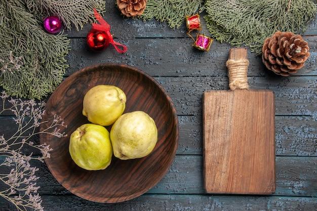 Vista dall'alto mele cotogne mature fresche frutti amari all'interno del piatto su pavimento rustico blu scuro frutta fresca di piante mature dell'albero
