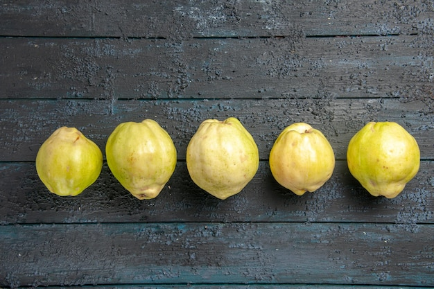 Vista dall'alto mele cotogne mature fresche frutti acidi allineati sull'albero da frutto rustico blu scuro della pianta da scrivania fresco maturo