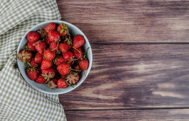 Top view of fresh ripe strawberries in a bowl on wood rustic with copy space
