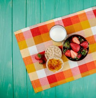 Vista dall'alto di fragole fresche mature in una ciotola di legno e torte di riso con marmellata e un bicchiere di latte sul tessuto plaid su legno verde con spazio di copia