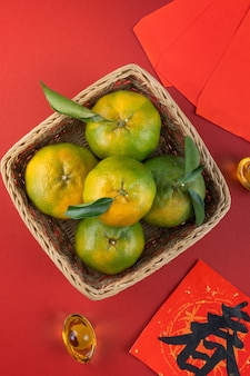 Top view of fresh ripe tangerine mandarin orange with fresh leaves on red table background for chinese lunar new year fruit concept, the chinese word means spring.