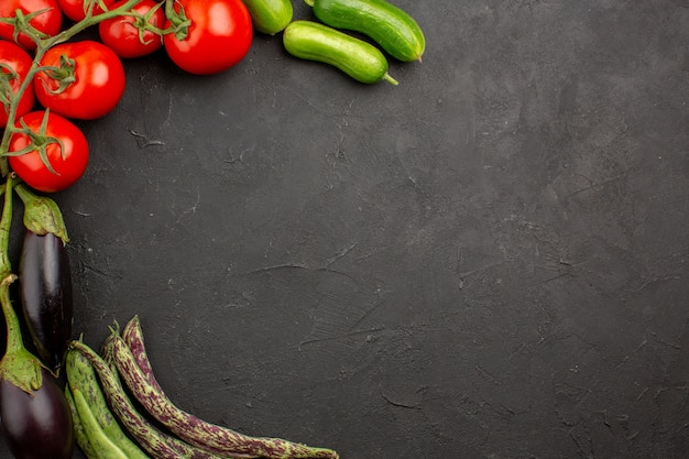 Top view fresh ripe vegetables composition on the dark background