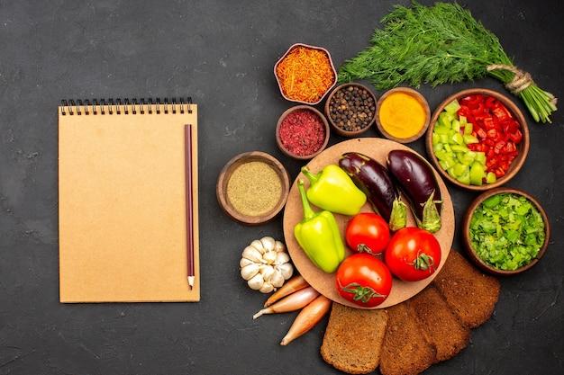 Вид сверху свежие спелые овощи с зеленью и темными буханками хлеба на темной поверхности салат еда еда здоровый овощ