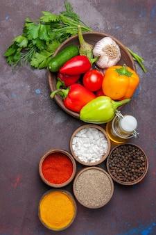 上面図新鮮な熟した野菜と緑と調味料の暗い表面のサラダミール野菜の熟した色