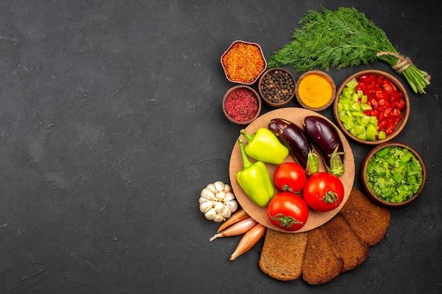Vista dall'alto verdure fresche mature con verdure e pagnotte di pane scuro sulla superficie scura insalata cibo pasto salute vegetale