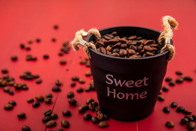 Vista dall'alto di chicchi di caffè tostati freschi su un cesto nero con chicchi di caffè isolati su uno sfondo rosso