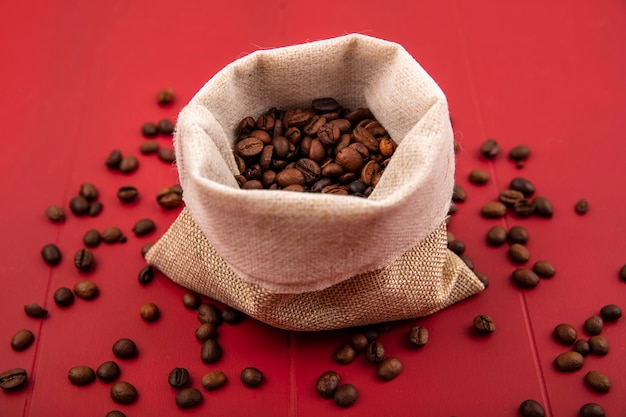 Top view of fresh roasted coffee beans on a burlap bag with coffee beans isolated on a red background