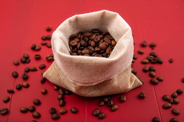 Vista dall'alto di chicchi di caffè tostati freschi su un sacchetto di tela da imballaggio con chicchi di caffè isolato su uno sfondo rosso