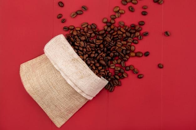 Vista dall'alto di chicchi di caffè tostati freschi che cadono da un sacchetto di tela da imballaggio su uno sfondo rosso