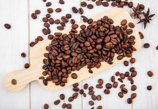 Vista dall'alto di chicchi di caffè tostati freschi isolati su uno sfondo di legno bianco