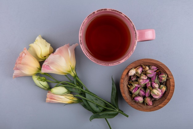 Top view of fresh rose buds on a wooden bowl with a cup of tea on a gray background