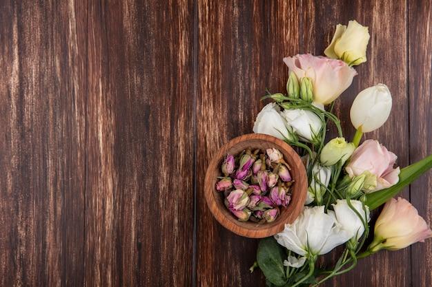 Vista dall'alto di rose fresche con boccioli di rosa su una ciotola di legno su uno sfondo di legno con spazio di copia