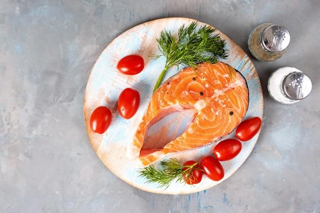 Top view of fresh salmon steak on light blue background