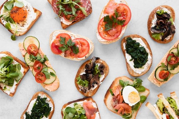 Вид сверху свежие бутерброды расположение на белом фоне