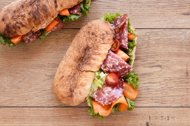 Top view fresh sandwiches assortment on wooden background