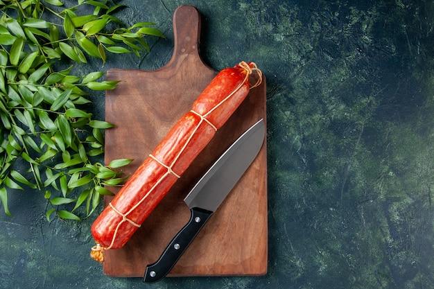 Вид сверху свежая колбаса с ножом и зелеными листьями на темно-синем фоне, хлебная булочка, мясо, бургер, цвет животного, еда, бутерброд
