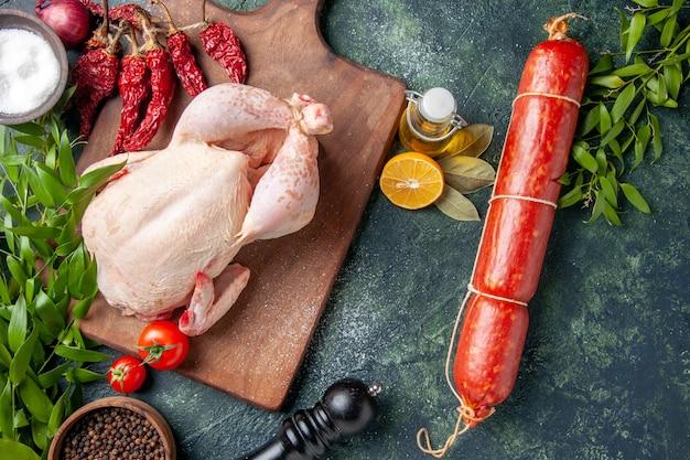 暗い背景色の生の鶏肉と新鮮なソーセージの上面図食品ハンバーガーミールサンドイッチ肉パン