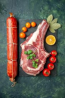 Vista dall'alto salsiccia fresca con pomodori e fetta di carne su uno sfondo chiaro-scuro panino carne cibo pane colore animale hamburger pasto
