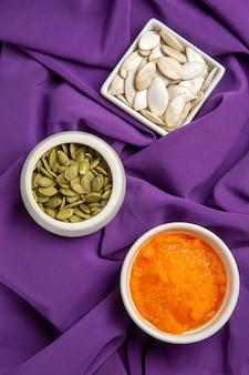 Vista dall'alto semi freschi con zucca schiacciata su frutta matura di semi di tessuto viola