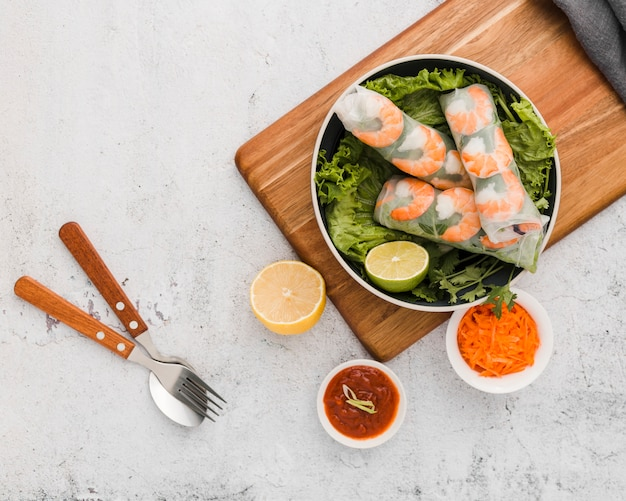 Top view of fresh shrimp rolls in bowl with sauce