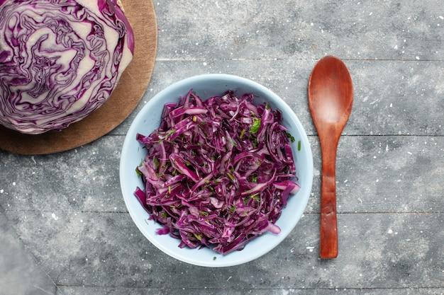 Вид сверху свежей нарезанной капусты фиолетовая капуста целиком и нарезанным на сером столе овощной салат свежие спелые
