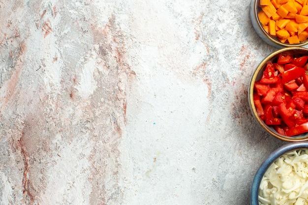 흰색 공간에 빨간 토마토와 후추와 상위 뷰 신선한 슬라이스 양배추