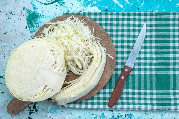 Vista dall'alto di cavoli freschi tagliati a fette e mezzo intero sulla scrivania blu brillante, insalata sana spuntino di cibo vegetale